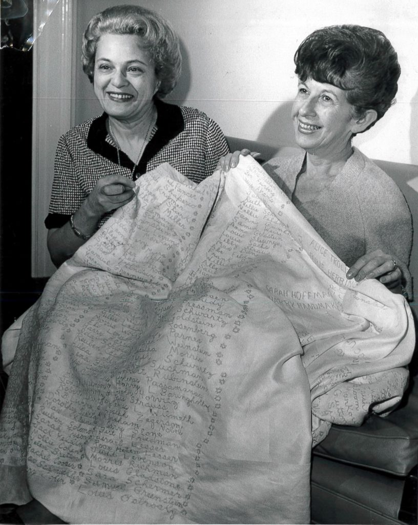 In 1965 after 11 years of work, Mrs. Morris Wheeler and Mrs. Bud Saunders showed off the completed Jewish Home and Hospital for the Aged tablecloth with more than 1200 names of individuals who made donations. (image courtesy Rauh Jewish History Program & Archives)